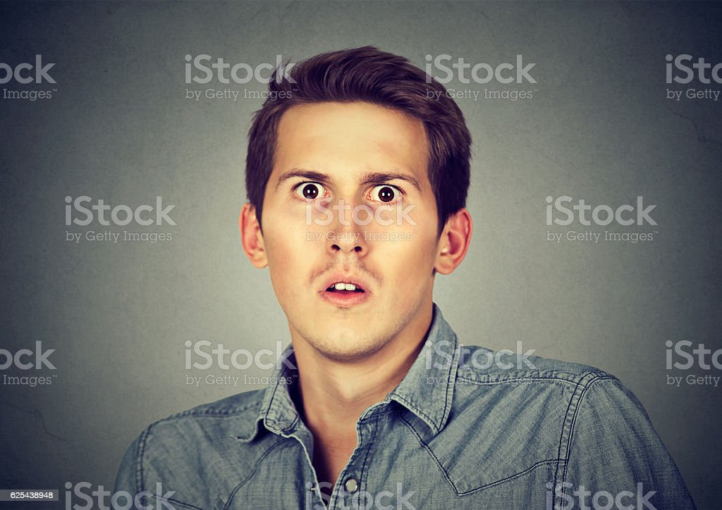 Closeup scared frightened young man stock photo