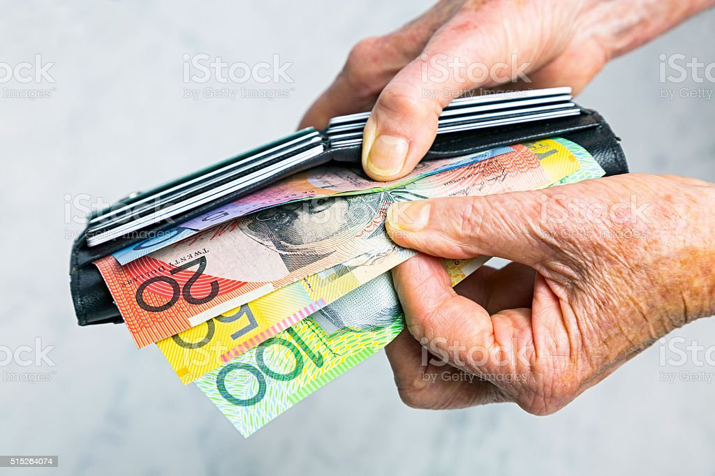 Close-up senior female hands taking Australian banknotes from purse stock photo