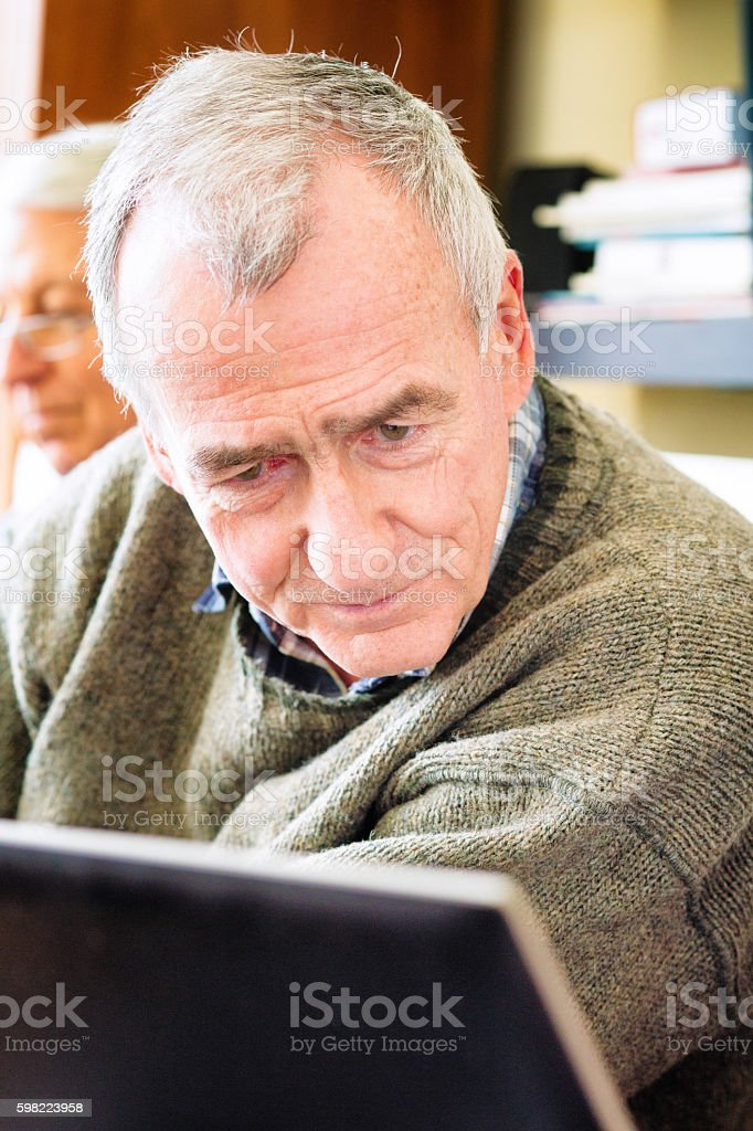 Close-up senior man looking at laptop with interest stock photo