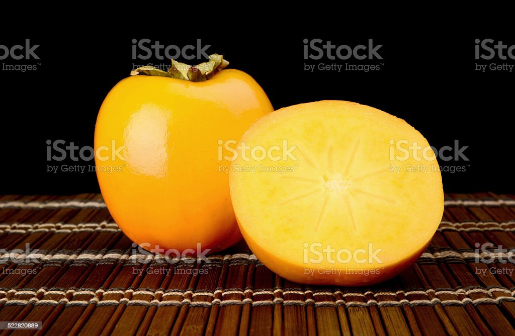Close-up shot many kakis sliced on mat isolated black stock photo