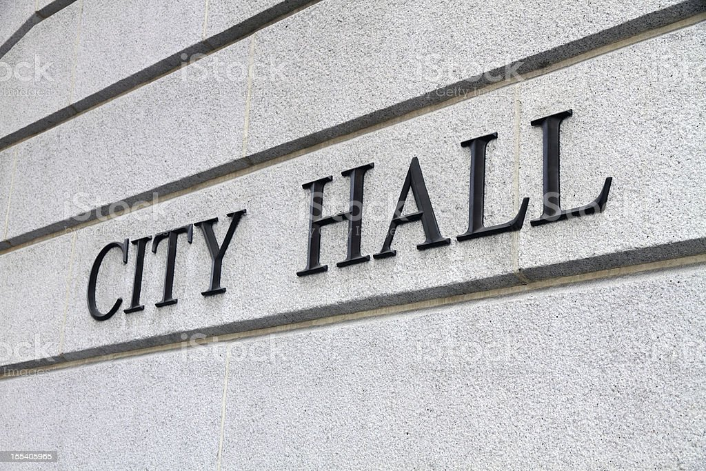 Close-up shot of a city hall sign on gray concrete wall stock photo