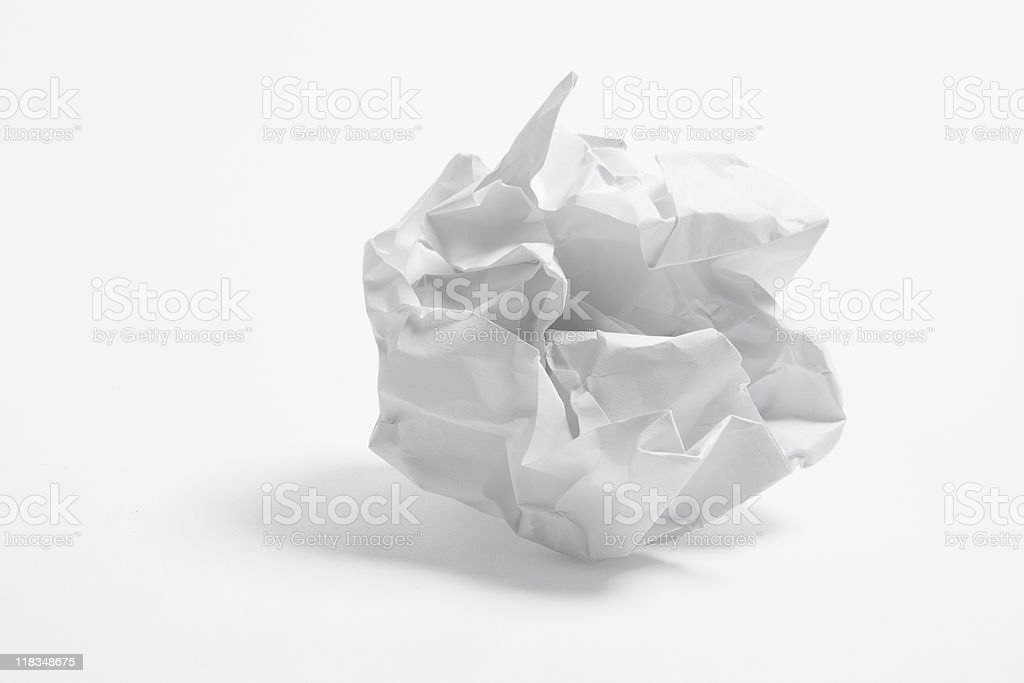 Close-up shot of a crumpled paper ball on a white backdrop stock photo