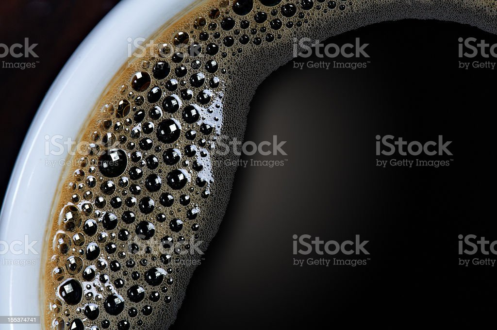 A closeup shot of a cup of black coffee with tiny bubbles  stock photo