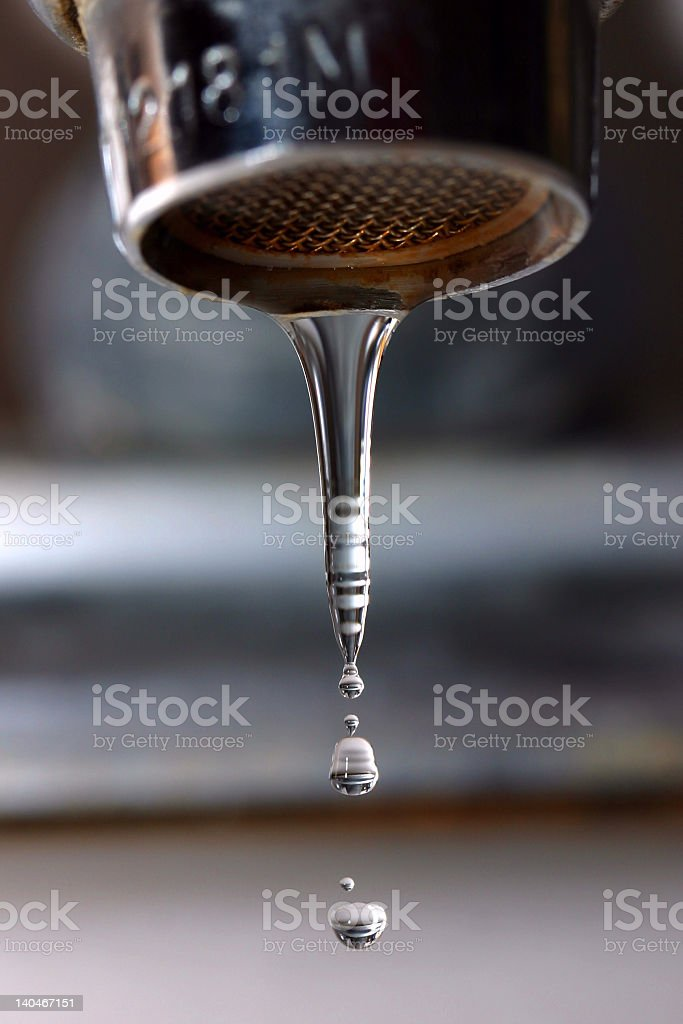 A close-up shot of a leaking faucet with water dripping royalty-free stock photo