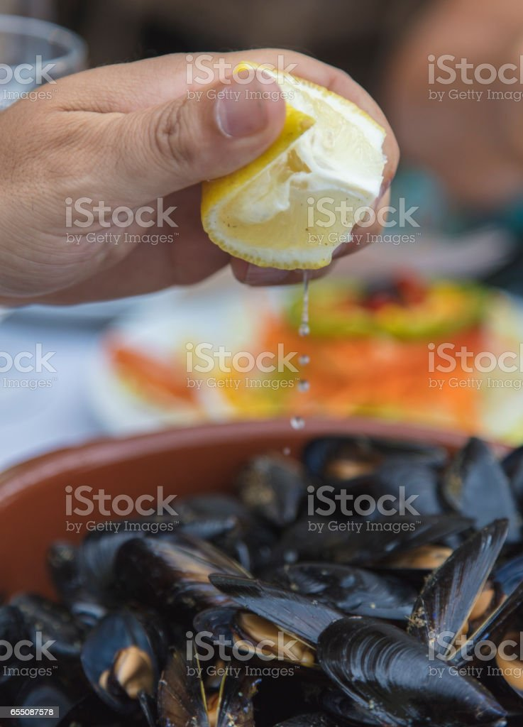 Close-up shot of a man's hand while he is squeezing a lemon edge over a bowl of fresh mussels. stock photo
