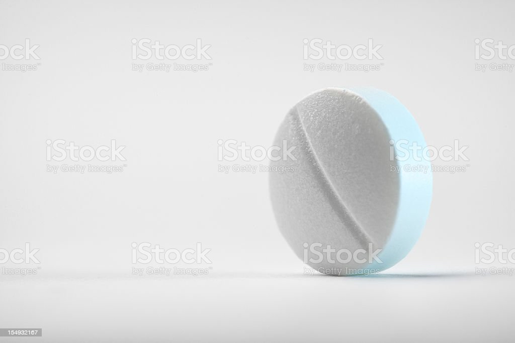 Close-up shot of a round pill on white background stock photo