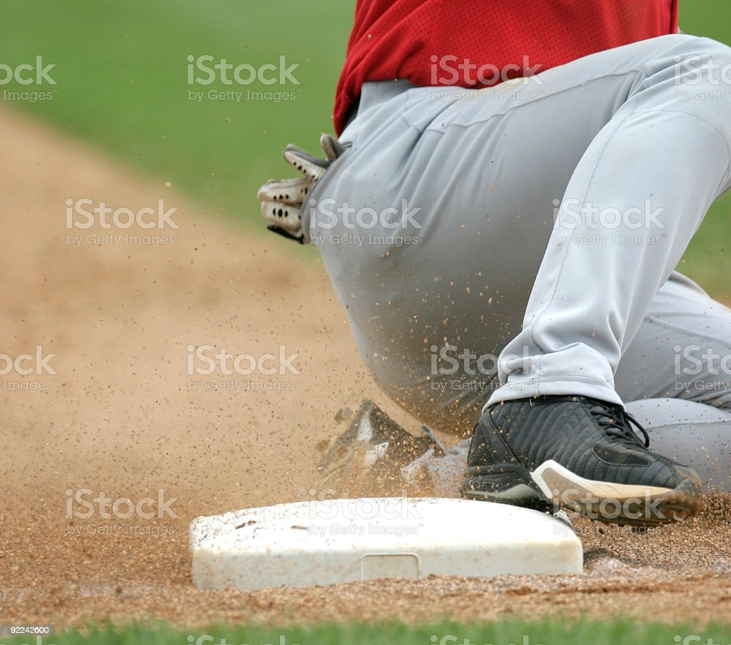 Close-up shot of baseball player sliding in to plate on sand stock photo