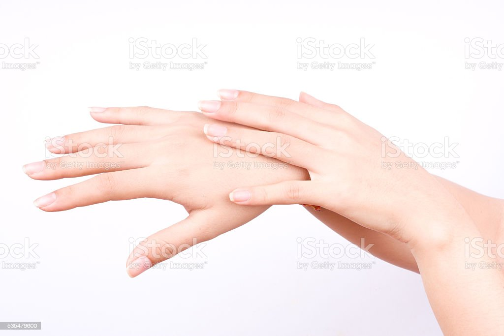 closeup shot of beautiful women hands applying hand cream stock photo