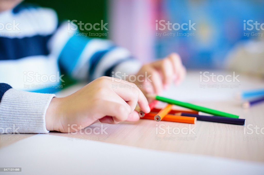 Closeup shot of boy hands playing with crayons stock photo