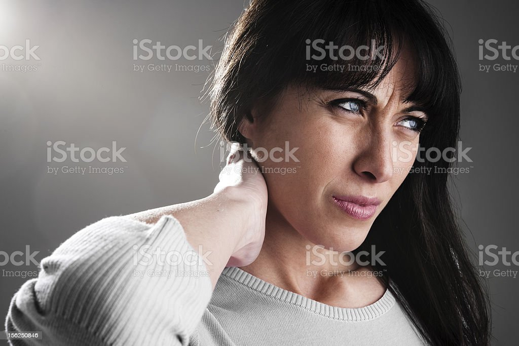 Close-up shot of brunette lady wincing from neck ache stock photo