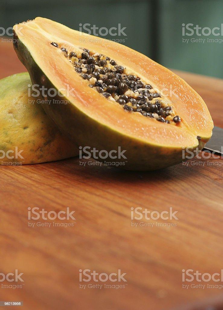 Close-up shot of half a papaya on a wooden chopping board stock photo