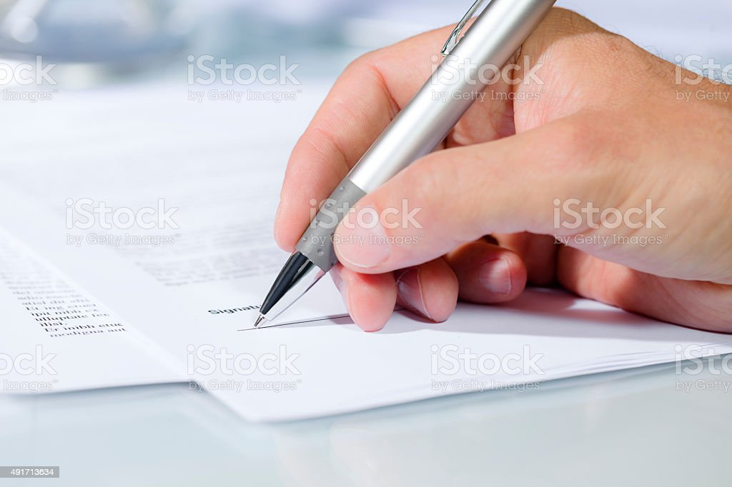 Close-up shot of hand signing a document stock photo