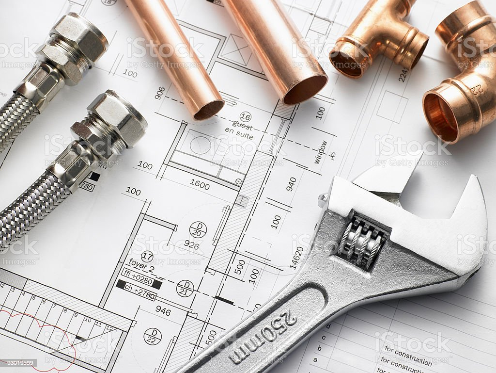 Closeup shot of plumbing equipment on house plans stock photo