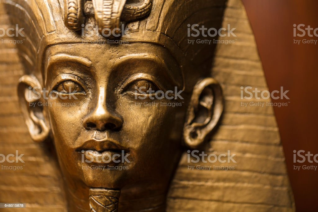 Close-up shot of the Egyptian King Tutankhamun's bust made out of a plaster mold and spray painted with bronze color after. stock photo