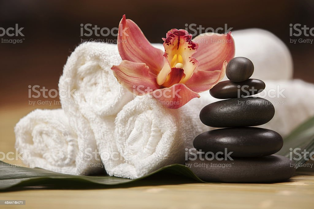 Close-up shot of towels, stones and a flower used for a spa stock photo