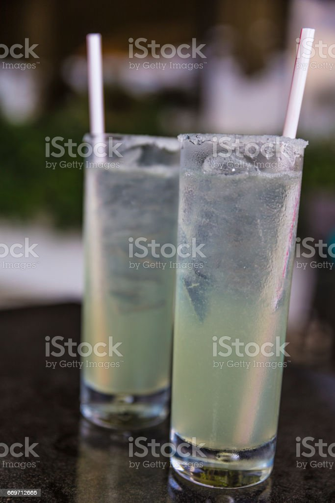 Close-up shot of two tall glasses of margarita with ice cubes and a drinking straws . stock photo