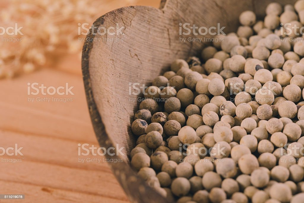 Close-up shot pepper with wood spoon on wooden background stock photo