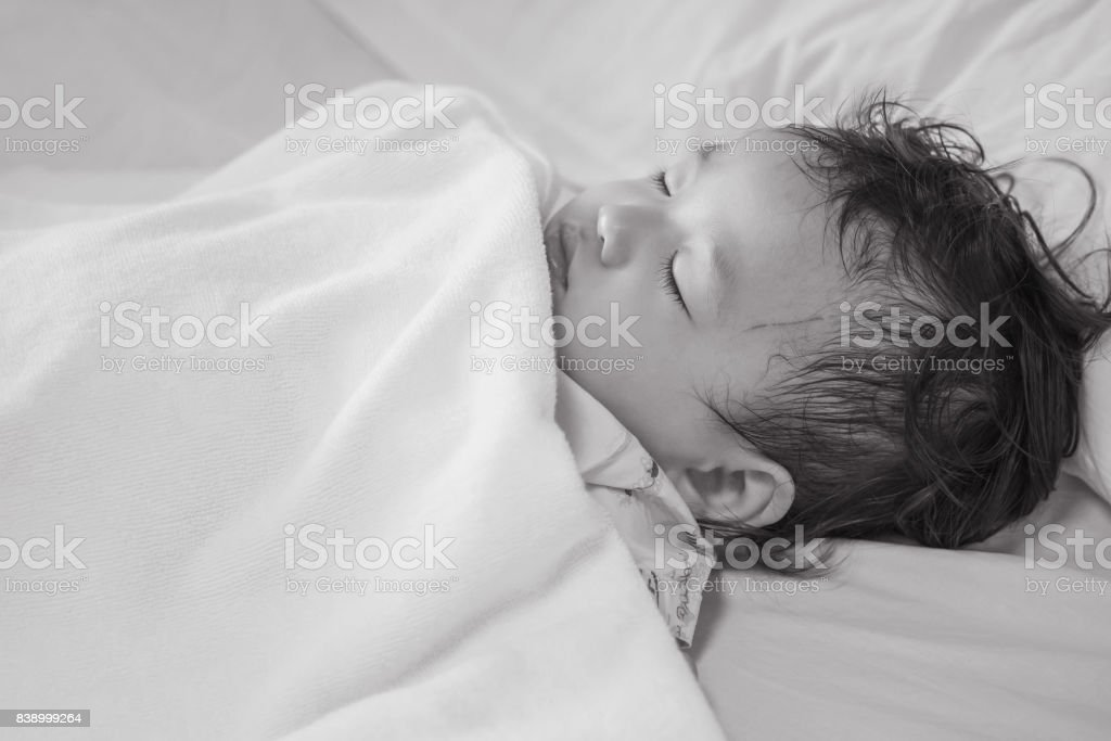 Closeup sick child sleep on hospital bed textured background in black and white tone stock photo