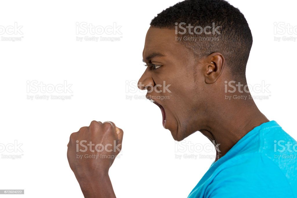 Closeup side view profile portrait angry upset young man worker business employee fists in air open mouth yelling stock photo