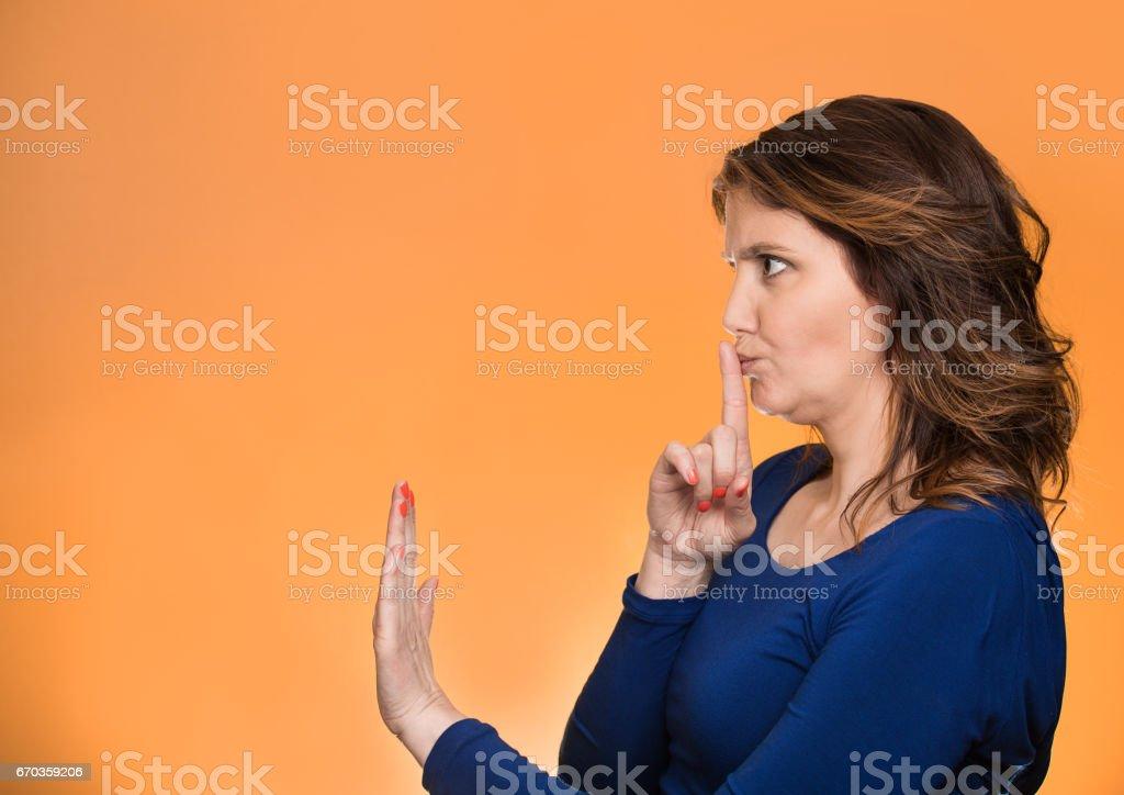 Closeup side view profile portrait serious woman finger, hand on lips, shhh gesture stock photo
