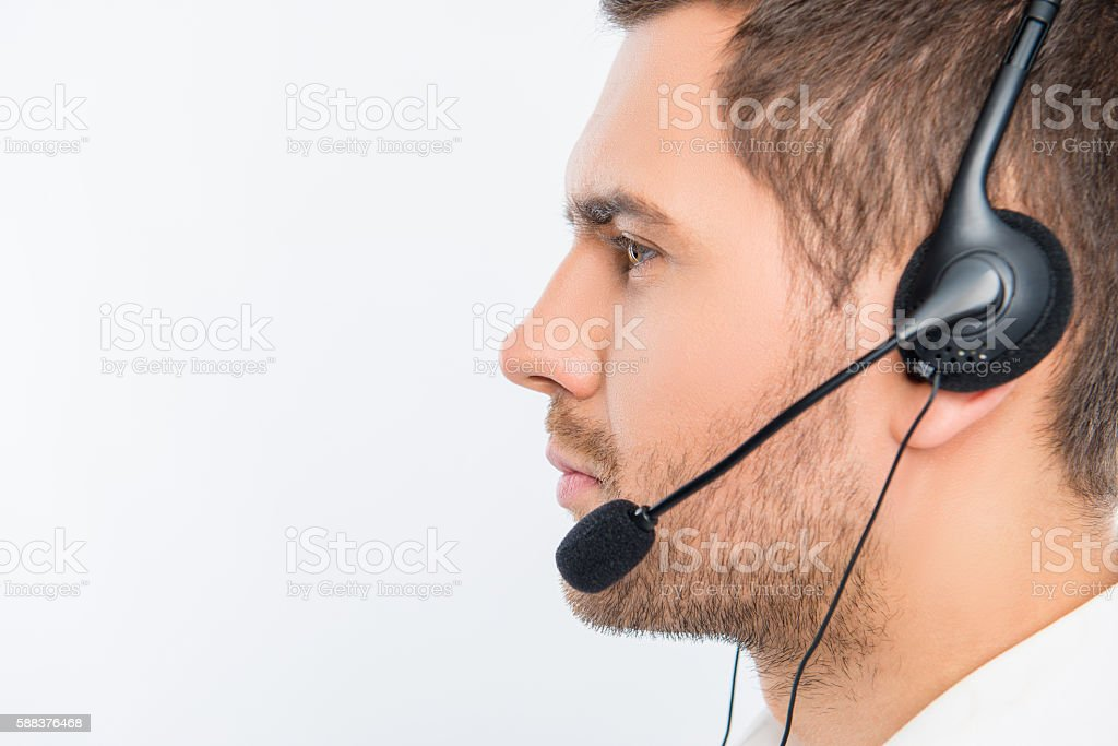 close-up side-face portrait of a young agent of call centre stock photo