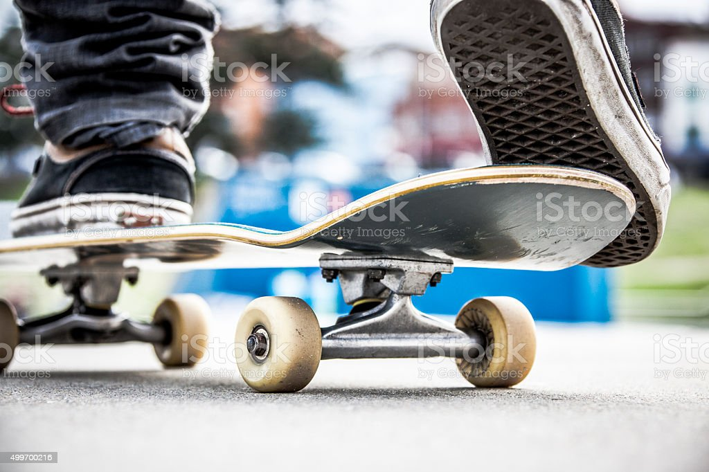 Close-up skateboarder balancing on skateboard ready for action stock photo