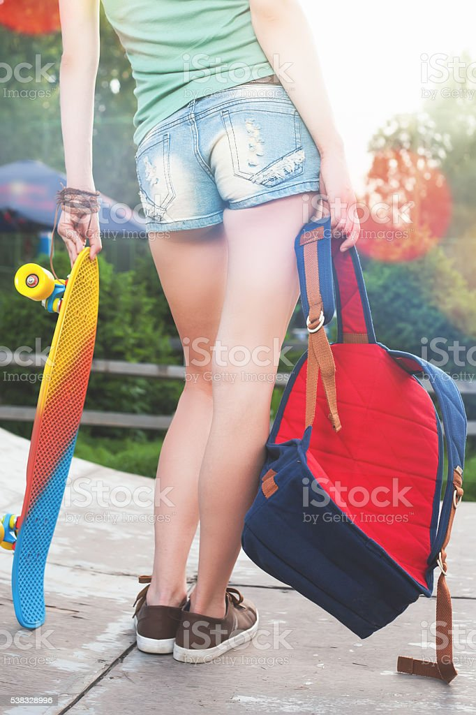 Close-up skateboarder girl with skateboard outdoor at skatepark stock photo