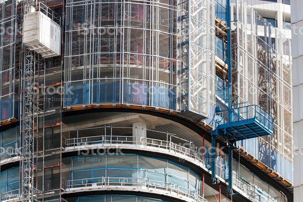 Closeup skyscraper construction with tower crane, platform and construction frame stock photo