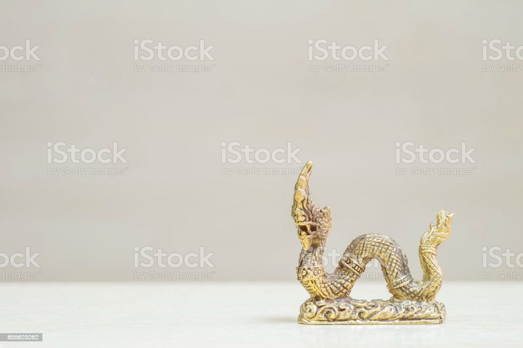 Closeup small brass king naga statue for worship and decorate on blurred wood desk and wood wall in room textured background stock photo