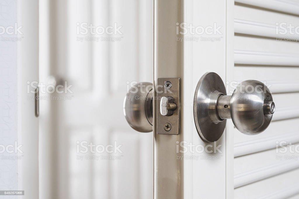 Close-up stainless door knob, with door open slightly stock photo