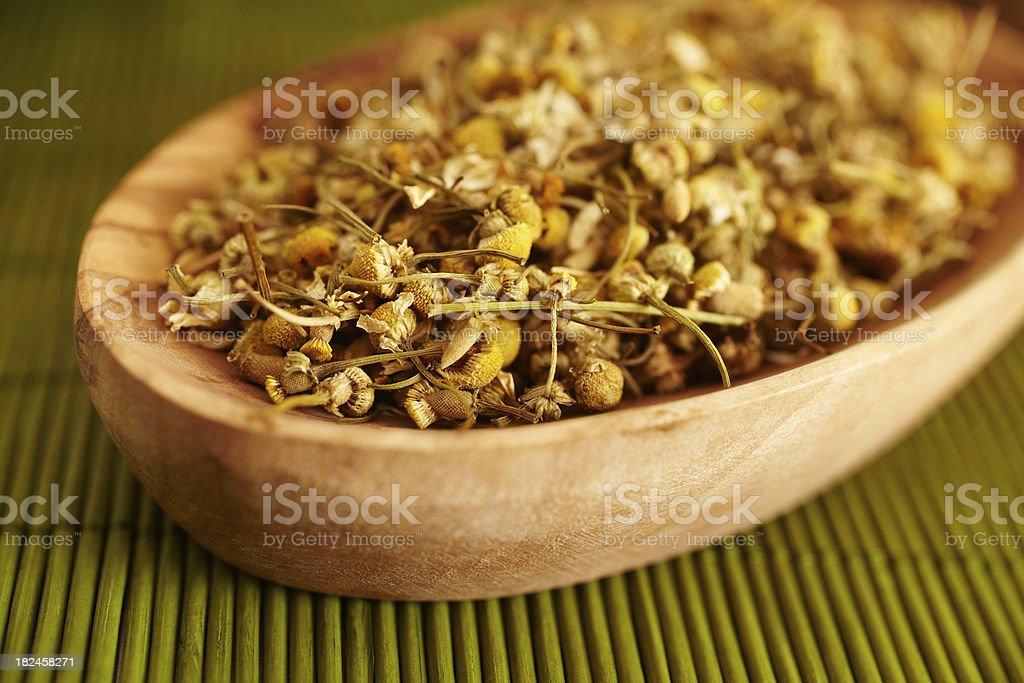 Close-up still life of Camomile flowers in wood bowl royalty-free stock photo