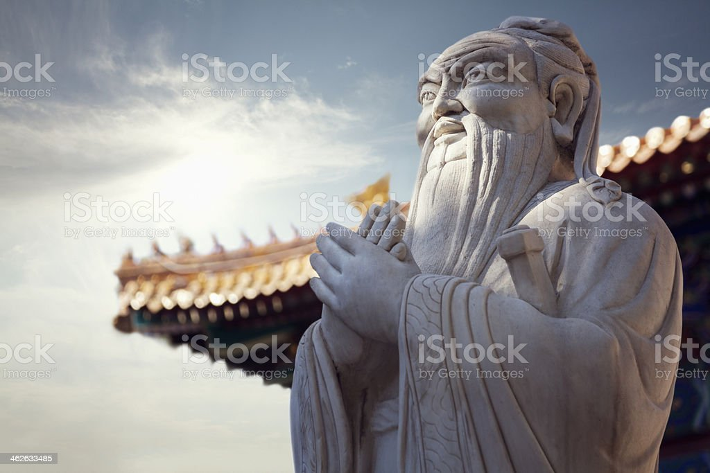 Close-up - stone statue of Confucius, pagoda roof in background stock photo