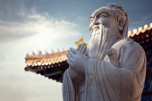 Close-up - stone statue of Confucius, pagoda roof in background