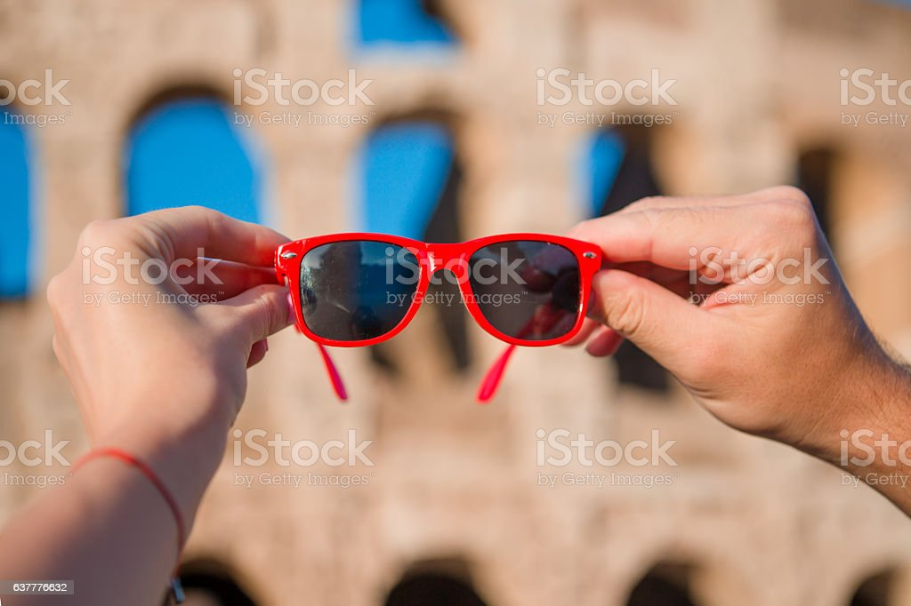 Closeup sunglasses in hands in front of Colosseum in Rome, stock photo
