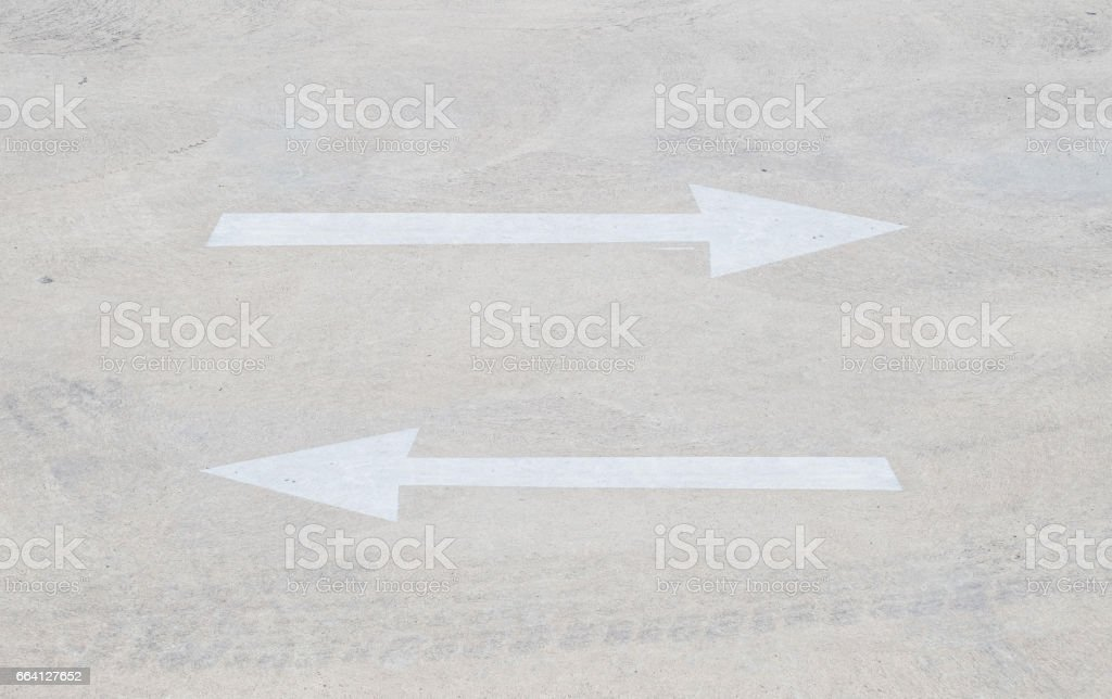 Closeup surface old and pale two white painted arrow sign in inverse side on cement street floor in the car park textured background stock photo