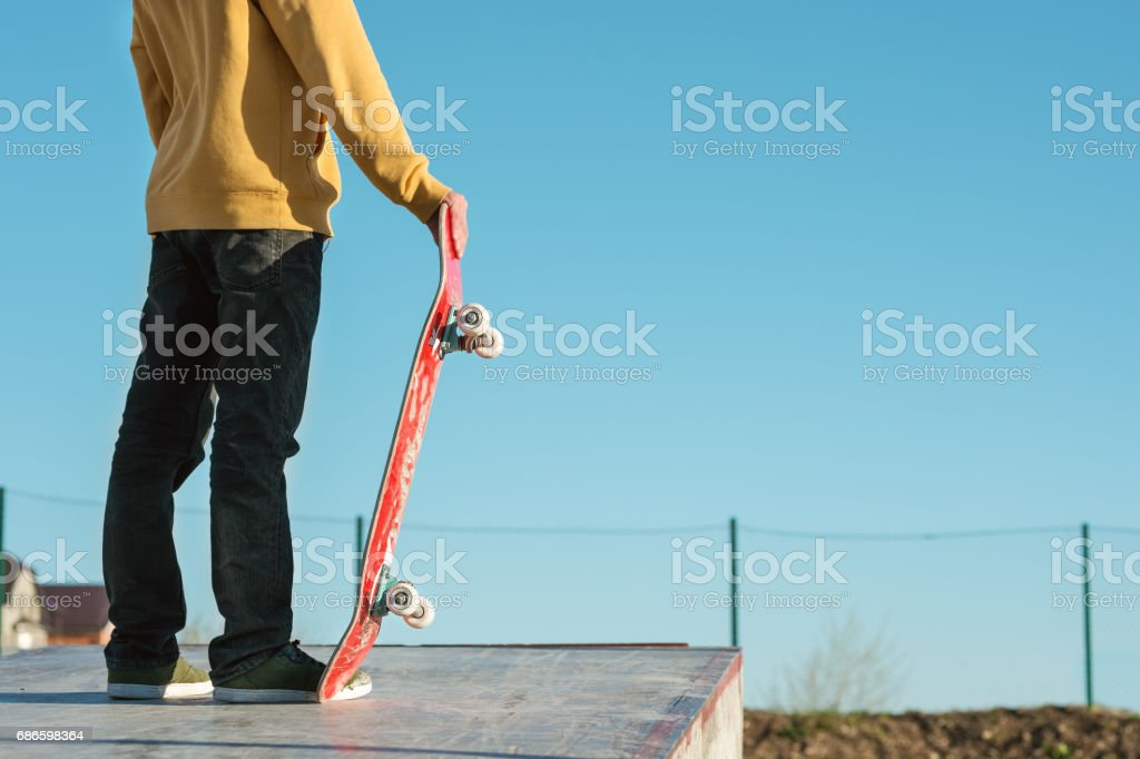 close-up Teenager standing in a yellow hoodie holding a hand skateboard on the background urban slum stock photo