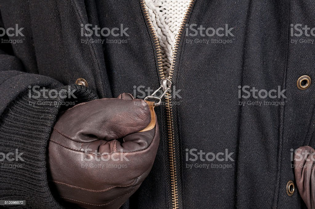Closeup texture of open zipper jacket hold with leather gloves stock photo