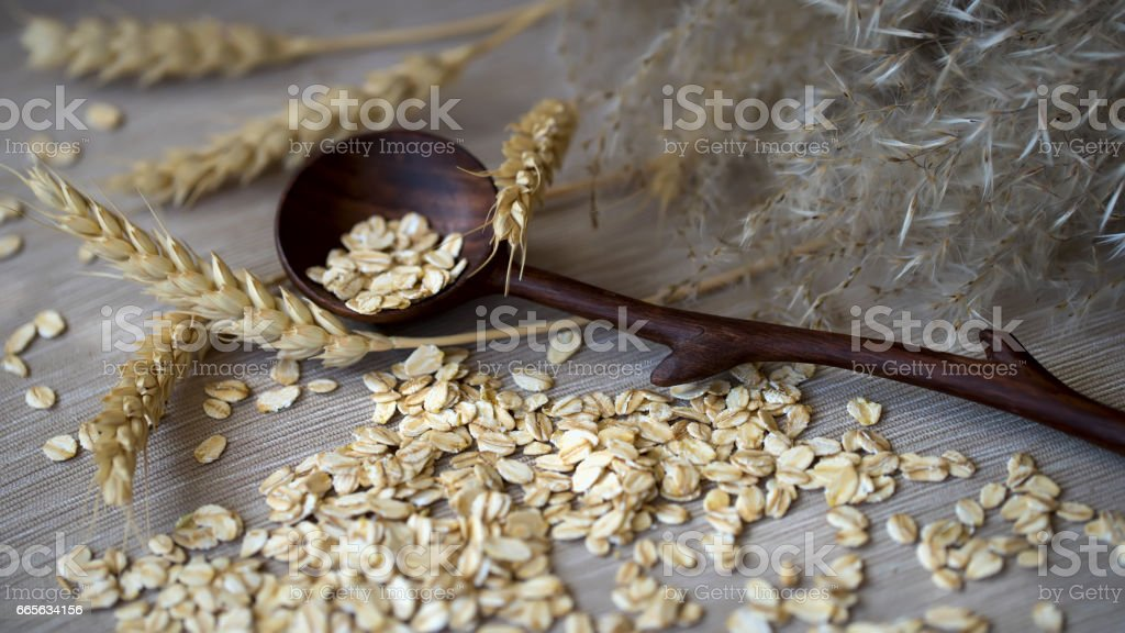 Close-up unprocessed Oat flakes with wooden spoon and different Ears against a plain coarse linen napkin. Concept of healthy food, right lifestyle, diet, vegan stock photo
