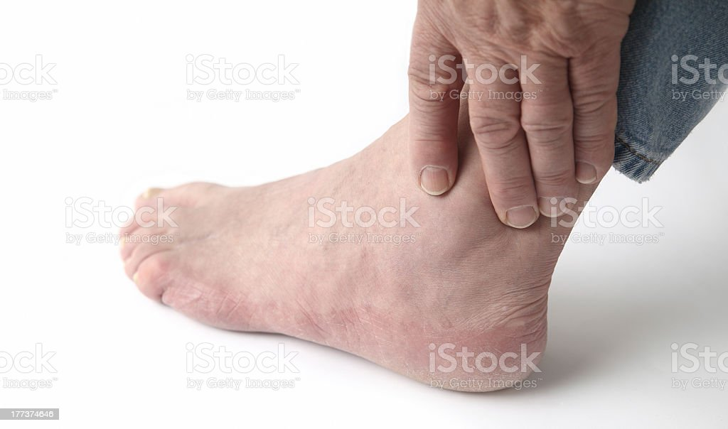 Close-up up of an ankle in pain being held stock photo