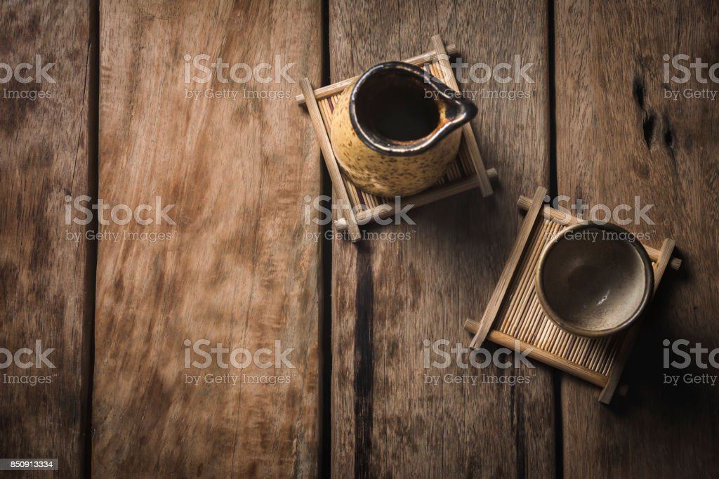 Close-Up variety of sake cups on ancient glass trays On the wooden table and the sun shines from the beautiful back. stock photo