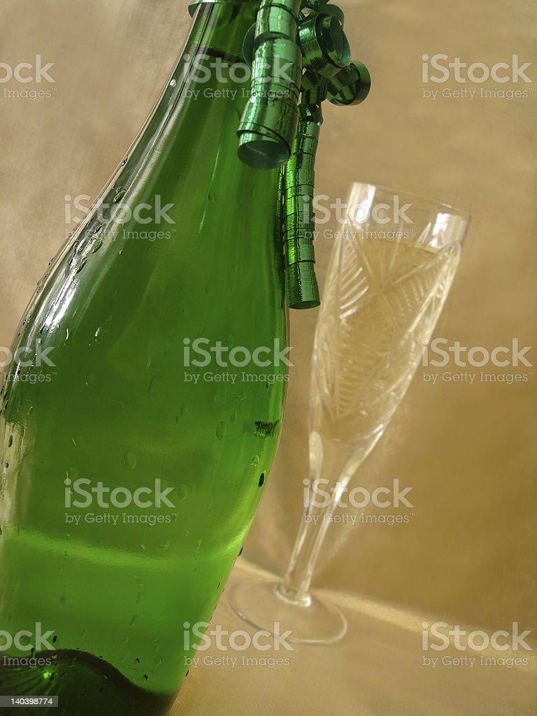 Close-up vista de garrafa de champanhe dourada e óculos no fundo foto de stock royalty-free