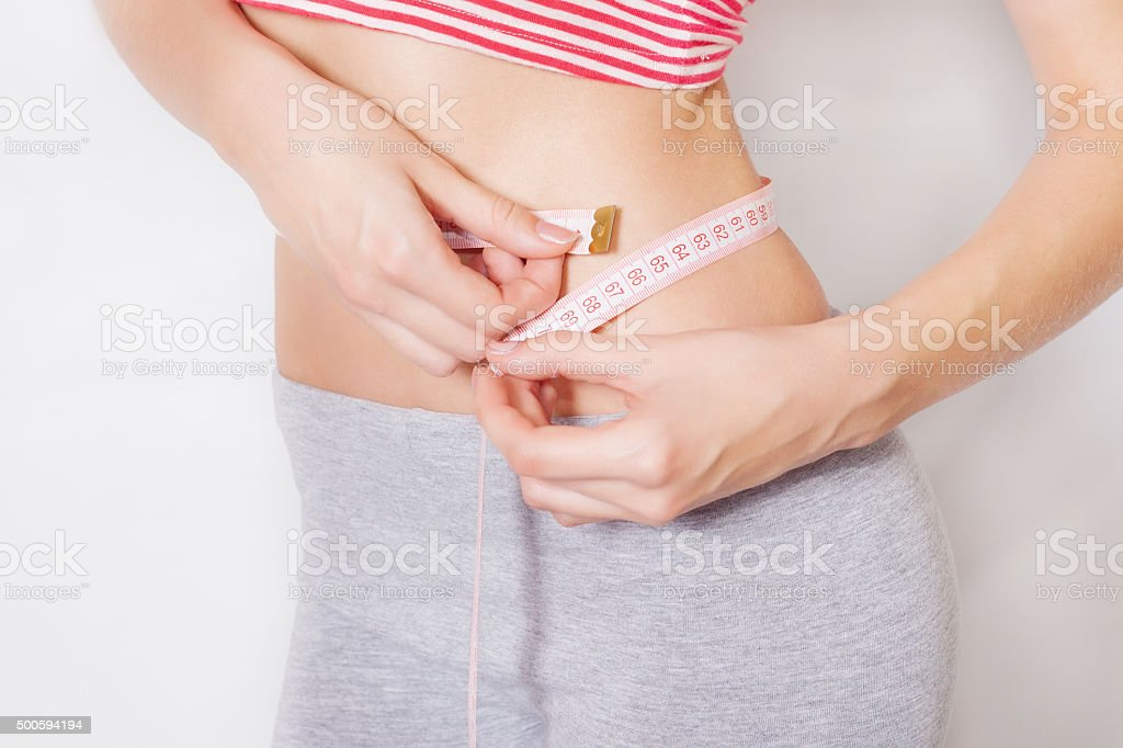 Closeup view of a gorgeous young woman with a measuring tape stock photo