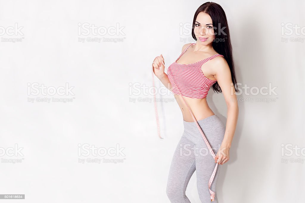 Closeup view of a gorgeous young woman with measuring tape stock photo