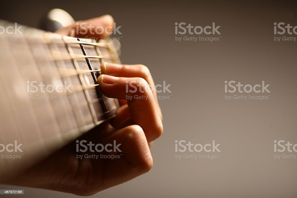 Close-up view of a six string acoustic guitar being held stock photo