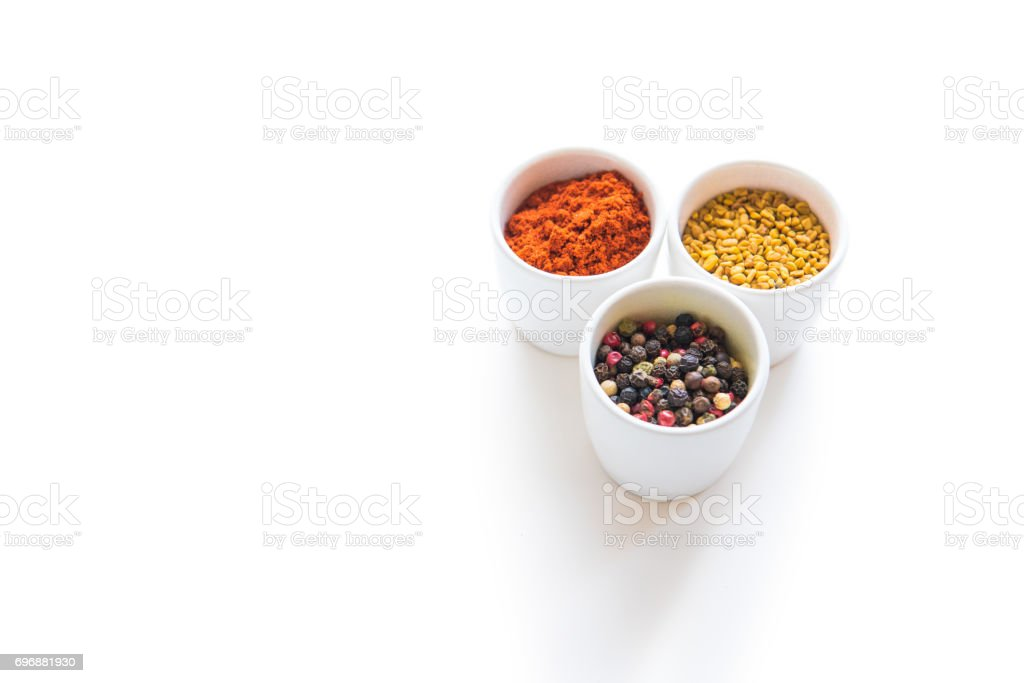 Close-up view of assorted aromatic dried spices in ceramic bowls isolated on white stock photo