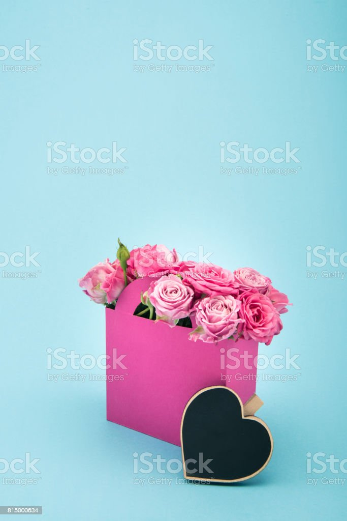 Close-up view of beautiful blooming pink roses in decorative paper bag and blank heart symbol isolated on blue stock photo
