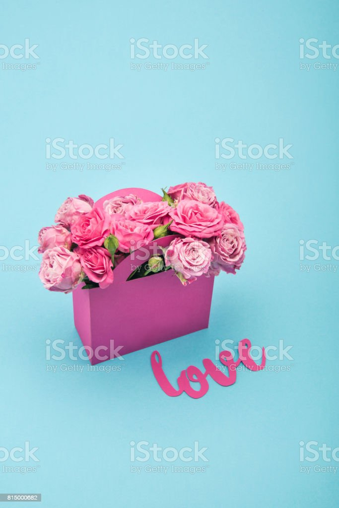 Close-up view of beautiful blooming pink roses in paper box and love symbol isolated on blue stock photo