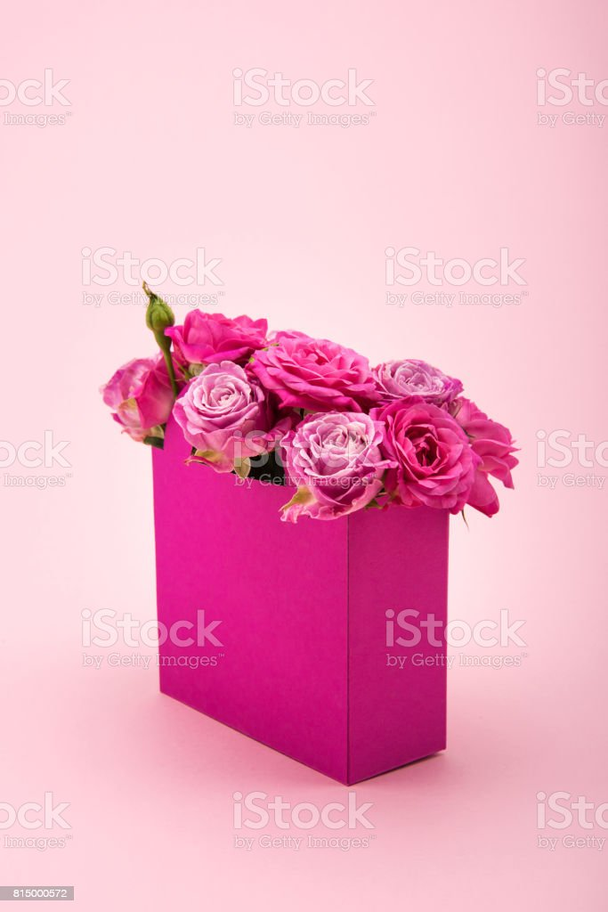 Close-up view of beautiful blooming rose flowers in decorative paper bag arranged isolated on pink stock photo