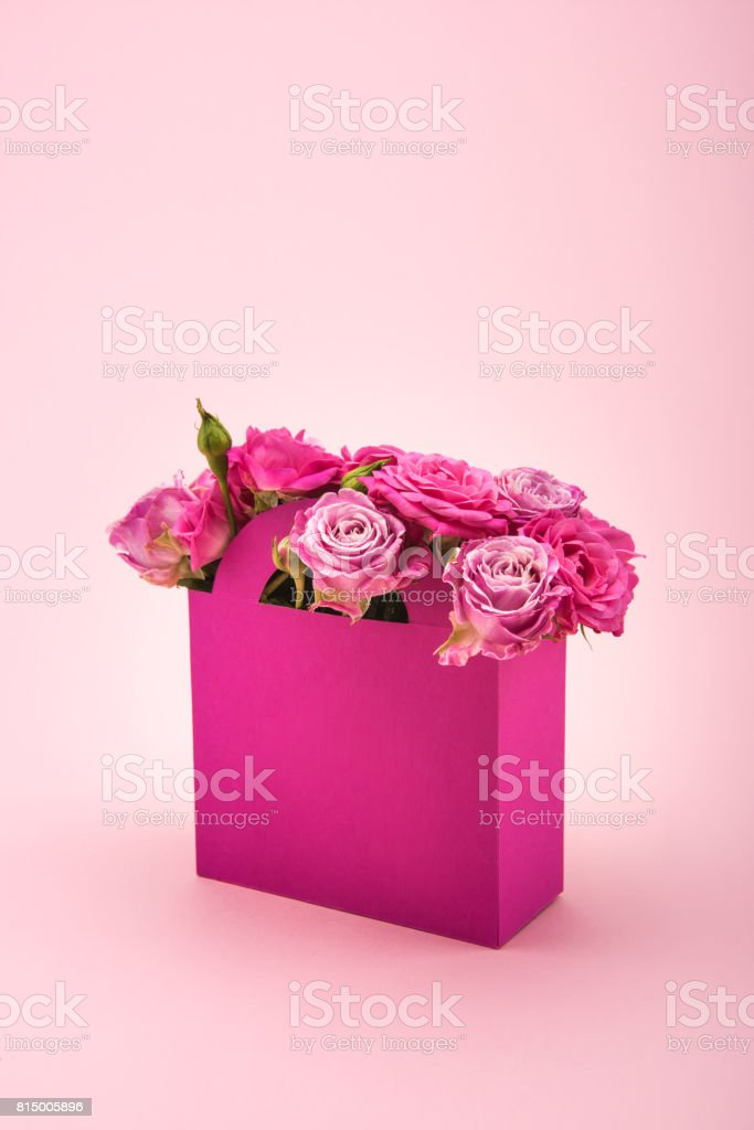 Close-up view of beautiful blooming rose flowers in decorative paper box arranged isolated on pink stock photo
