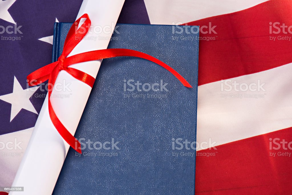 Close-up view of diploma and book on american flag, education concept stock photo